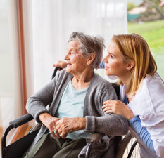 elderly woman on wheelchair and caregiver looking at distance